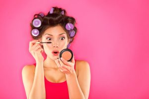 Makeup mascara woman with hair rollers